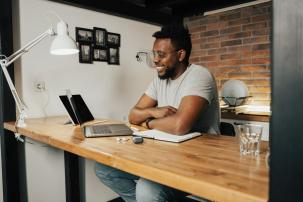 Man sat at desk in front of laptop. Table is oak and backgroud is bare brick with one white wall. Man is wearing a grey t-shirt.